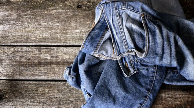 Eine dreckige Jeans liegt auf dem Boden.