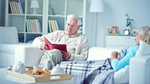 Ein älterer Mann sitzt mit seiner Frau auf dem Sofa und liest.