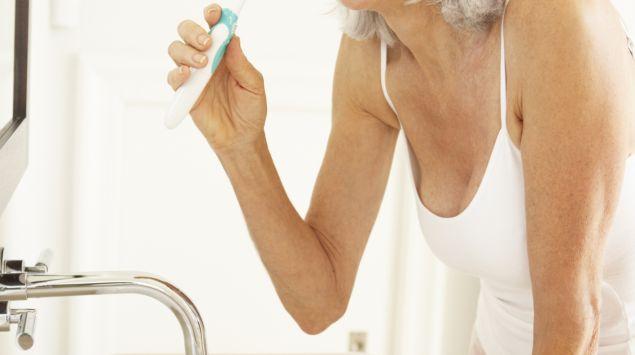 Man sieht eine ältere Frau am Waschbecken, die sich die Zähne putzt.