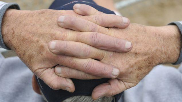 Ein älterer Mann hat die Hände auf dem Kopf verschränkt.