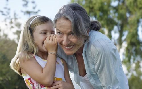 Ein kleines Mädchen flüstert einer älteren Frau etwas ins Ohr.