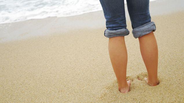 Eine Person steht barfuß am Strand.
