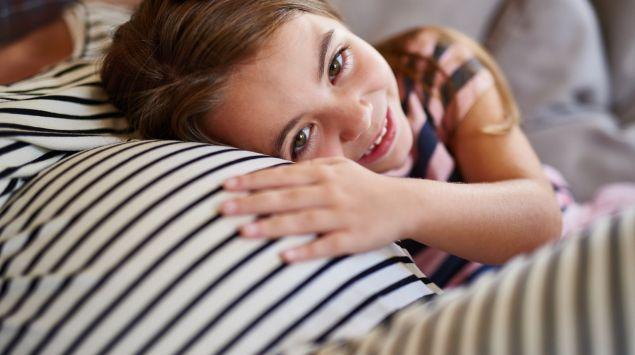 Ein kleines Mädchen hält ein Ohr und eine Hand an den Bauch einer Schwangeren.