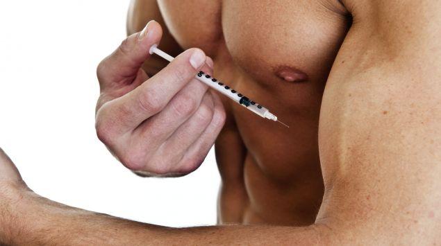 Das Bild zeigt einen muskulösen Mann, der sich Anabolika in den Arm spritzt.