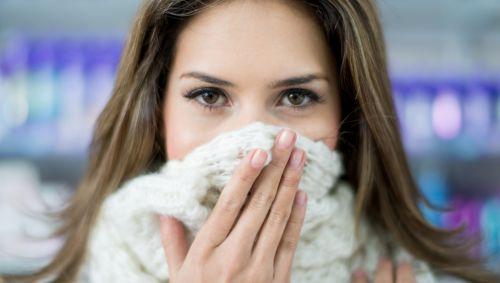Eine Frau hat sich den Schal vor Mund und Nase gezogen.