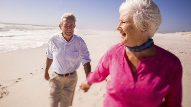 Ein älteres Pärchen läuft einen Strand entlang.