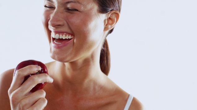 Man sieht eine lachende junge Frau mit einem Apfel in der Hand.