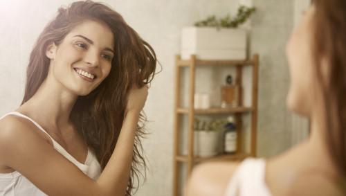Eine Frau bewundert ihre schönen Haare.