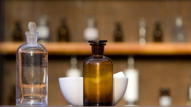 Auf einem Tisch vor einem regal stehen altmodische Apothekerflaschen und ein Mörser.