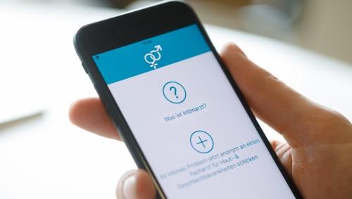 Hand hält Smartphone, auf dem die App Intimarzt geöffnet ist