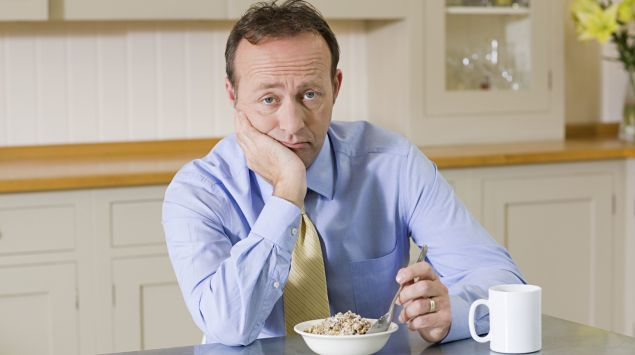 Ein Mann mittleren Alters sitzt in der Küche und stochert lustlos in seinem Müsli herum.