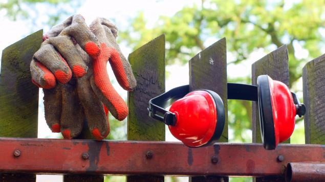 Arbeitshandschuhe und Lärmschutz hängen an einem Holzzaun.