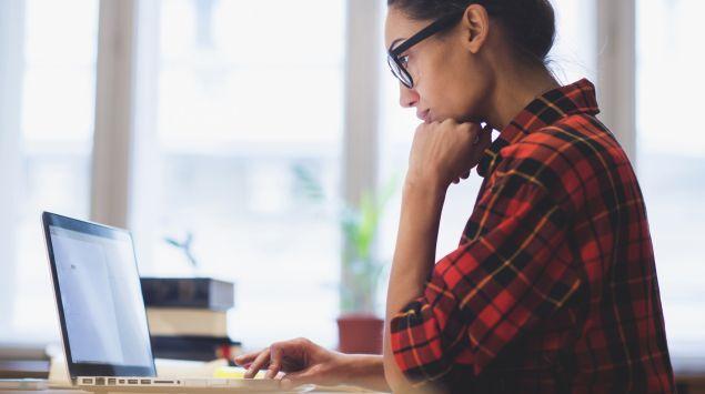 Eine Frau schaut auf einen Laptop.
