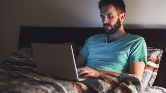 Ein Mann sitzt mit seinem Laptop im Bett.