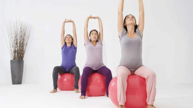 Drei Schwangere auf Gymnastikbällen dehnen die Arme.