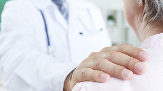 Ein Arzt legt seiner älteren Patientin beruhigend eine Hand auf die Schulter.