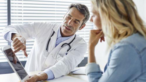Der Arzt erklärt der Patientin etwas.
