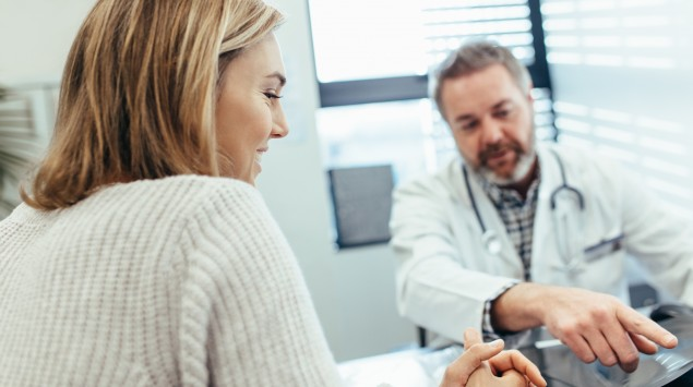 Ein Arzt erklärt einer Patientin etwas.