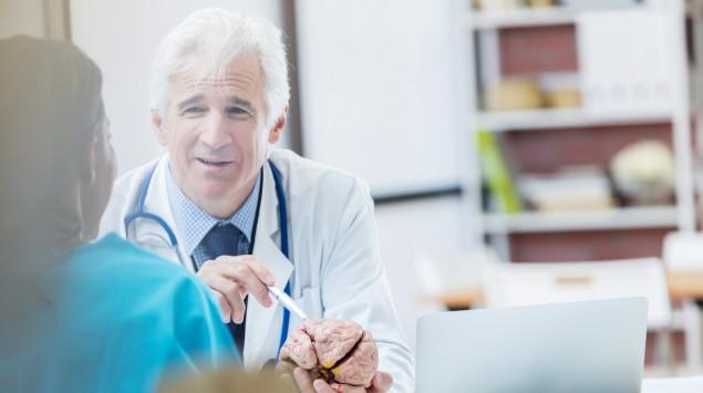 Ein Arzt erklärt etwas einer Patientin, er hat ein Gehirnmodell in der Hand.