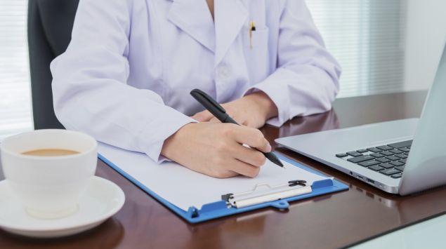 Ein Arzt sitzt am Schreibtisch und macht sich Notizen.