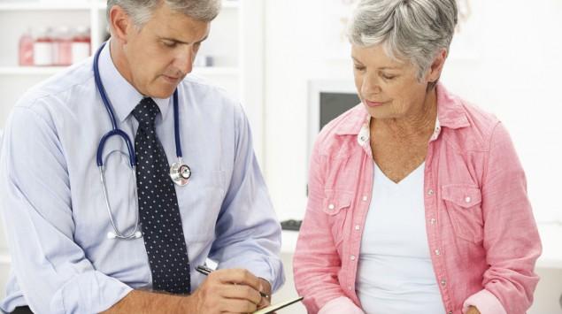 Ein Arzt im Gespräch mit einer älteren Patientin.