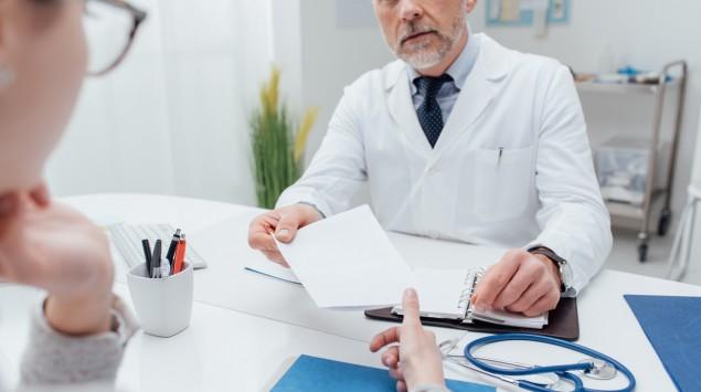 Ein Arzt und eine Patientin am Schreibtisch.