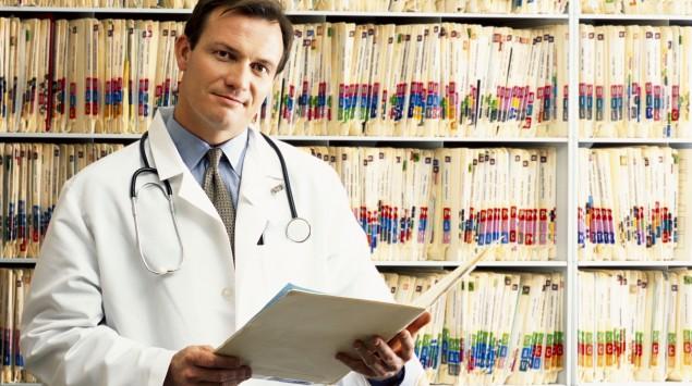 Ein Arzt steht vor einem Regal mit Akten.