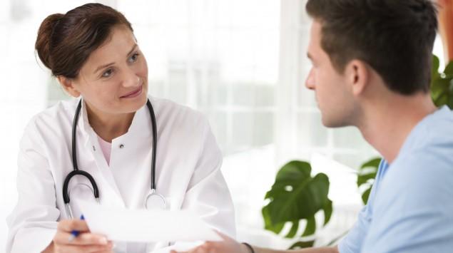 Man sieht eine Ärztin im Gespräch mit einem Patienten.