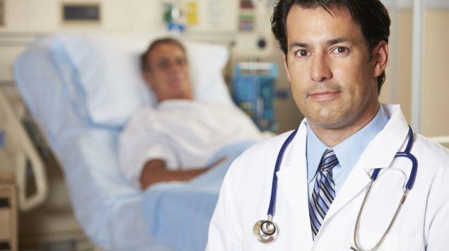 Das Bild zeigt im Vordergrund einen Arzt und im Hintergrund einen Patienten.