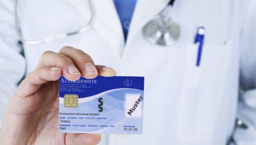 Ein Arzt hält seinen Arztausweis hoch.
