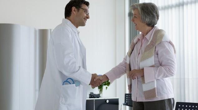 Eine Frau begrüßt einen Arzt.