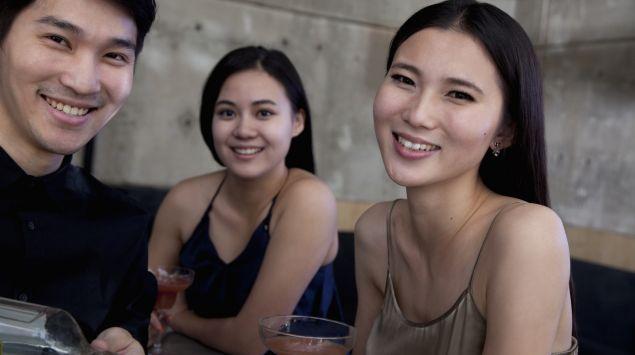 Drei Asiaten trinken Alkohol.