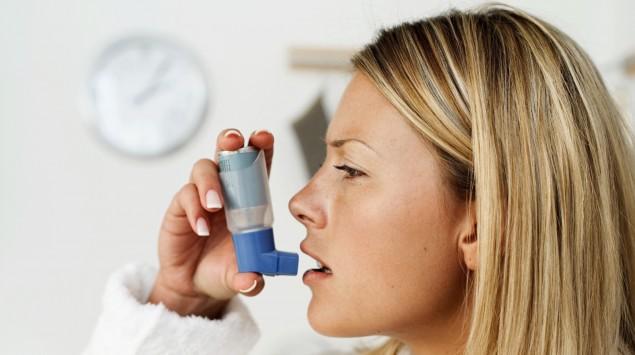 Eine Frau benutzt ein Asthmaspray.