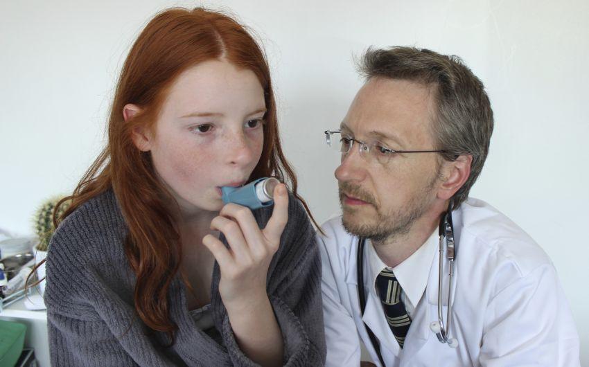 Das Bild zeigt ein junges Mädchen, das unter Anleitung eines Arztes ein Asthmaspray benutzt.