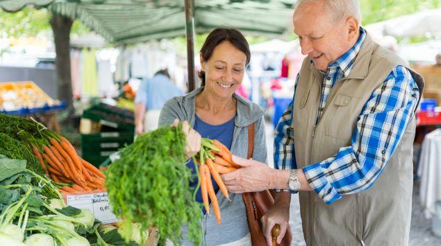 Eine Frau mit einem älteren Herrn auf dem Wochenmarkt.