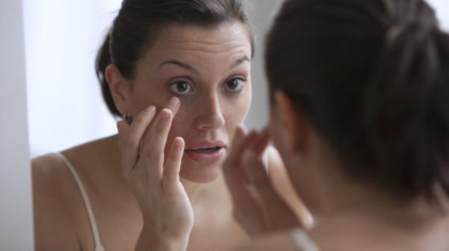 Eine Frau mit endokriner Orbitopathie untersucht ihre Augen im Spiegel.