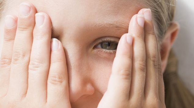 Ein Mädchen schaut zwischen ihren Händen hindurch.