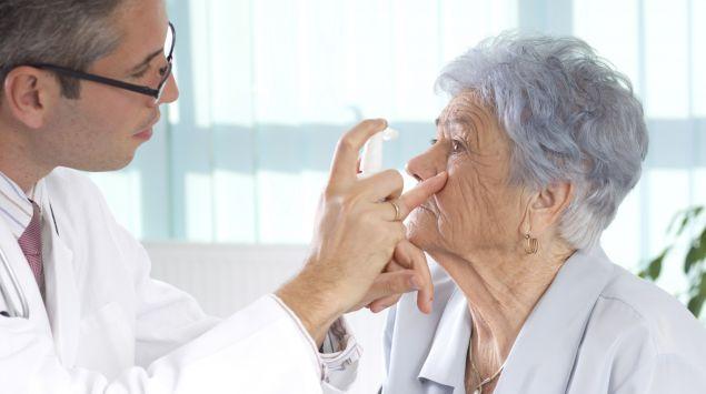 Ein Arzt betrachtet eine Stelle unterhalb des Auges bei einer älteren Frau.