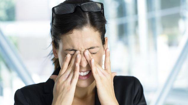 Eine Frau hält sich die Hände an die schmerzenden Augen.