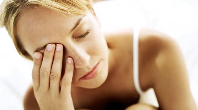 Eine Frau hat die Augen geschlossen und fasst sich an das rechte Auge.