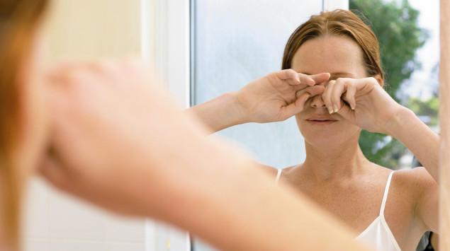Eine Frau steht vor dem Spiegel und reibt sich die Augen: Schlafmangel ist eine Ursache für geschwollene Augen