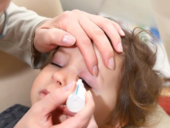 Ein Kind bekommt Augentropfen.