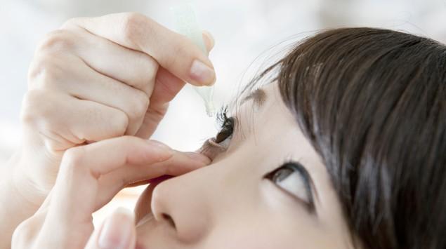 Eine Frau verabreicht sich Augentropfen.
