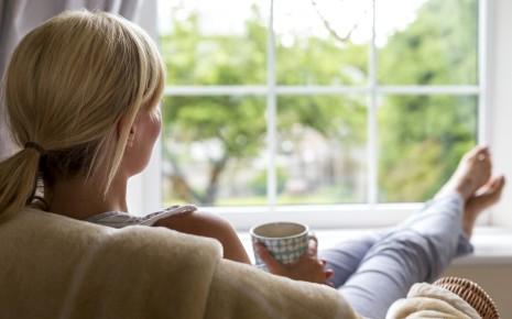 Burnout-Syndrom: Eine Frau sitzt im Sessel, hält eine Tasse in den Händen und schaut aus dem Fenster.