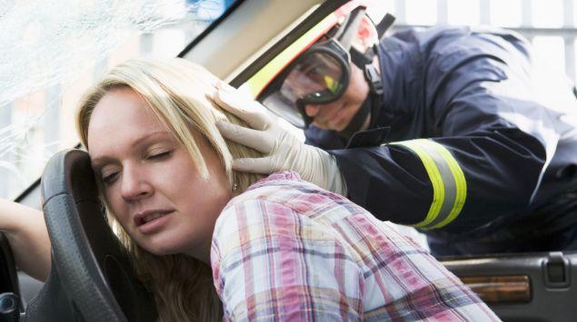 Ein Feuerwehrmann überprüft den Zustand einer bewusstlosen Frau im Auto.