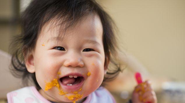 Ein Baby isst Babybrei.
