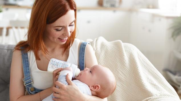 Mutter füttert ihr Baby mit der Flasche