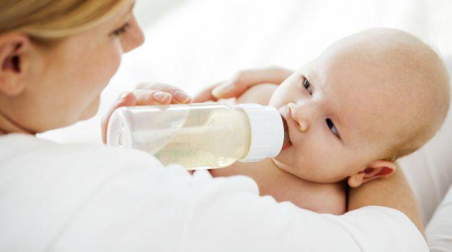 Das Bild zeigt eine Frau, die ihr Baby mit der Flasche füttert.