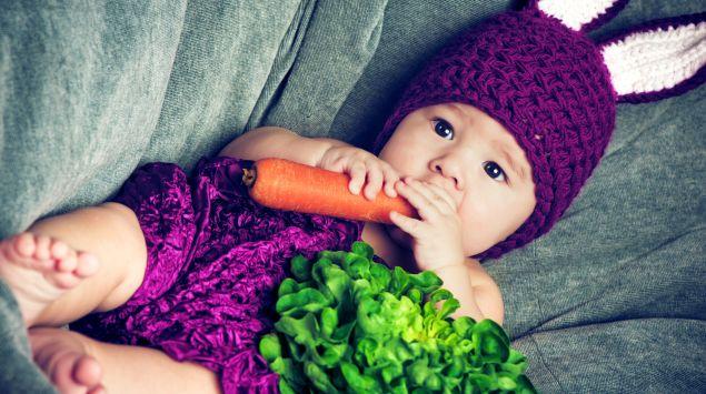 Ein Baby, als Hase verkleidet, mit Möhre und Salat.