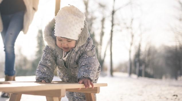 Warm angezogenes Baby mit Mutter in Winterlandschaft.